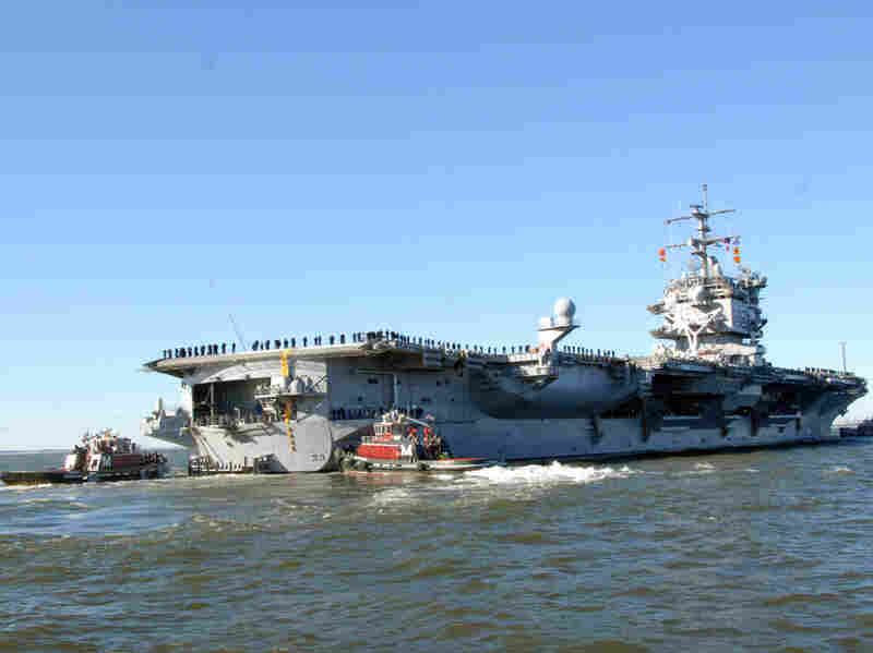 The aircraft carrier USS Enterprise, shown departing from Naval Station Norfolk on Jan. 13, is now in the Red Sea, with its dozens of warplanes, waiting to see if it's needed for any Libyan operation.