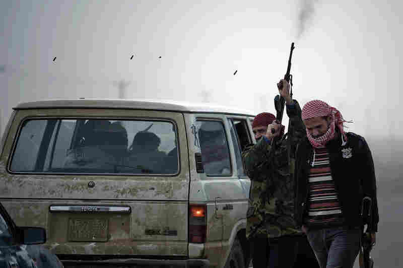 A Libyan rebel fighter fires his rifle in the air at Ajdabiya's west gate on Friday.