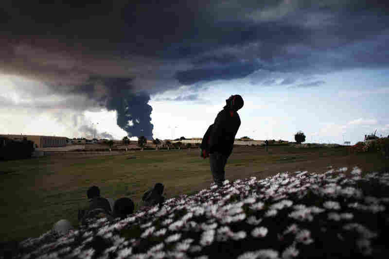 Libyan rebels watch smoke rising from an oil pipe just outside the town of Ras Lanuf, where many anti-regime fighters retreated after artillery and airstrikes from government troops Wednesday.