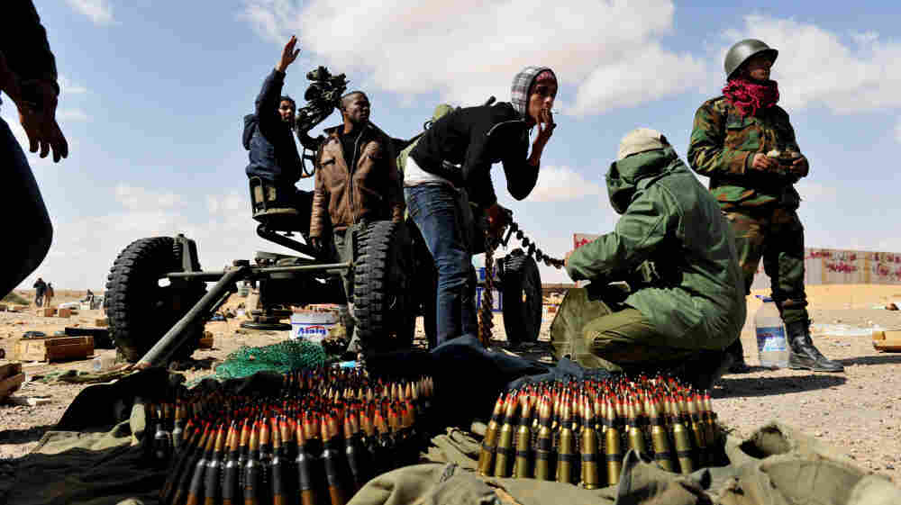 Rebel fighters loaded ammunition into an anti-aircraft machine gun Tuesday as Libyan air force fighter jets flew overhead in the oil-rich town of Ras Lanuf.
