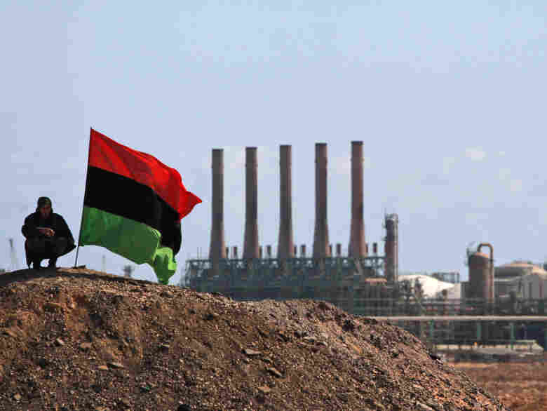 An opposition fighter perches next to a pre-Gadhafi flag as he stands guard outside the oil refinery in Ras Lanuf.