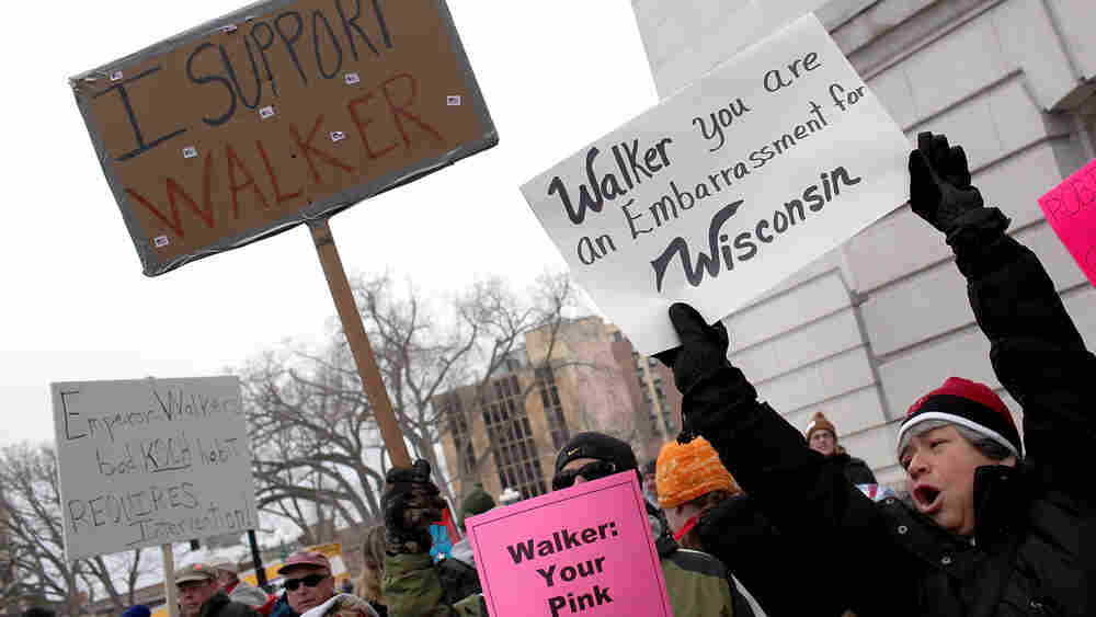 Labor and union supporters protest alongside supporters  of Wisconsin governor Scott Walker outside the State Capitol on Saturday  in Madison.