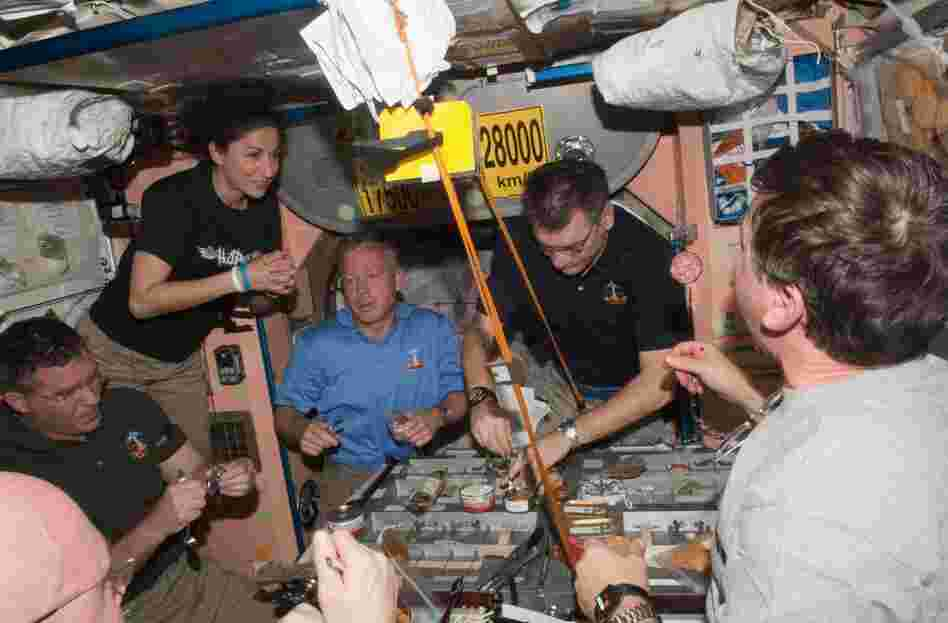 Space station and Discovery crew members share a meal. From left: Steve Bowen, Nicole Stott, Steve Lindsey, Paolo Nespoli and Michael Barratt.