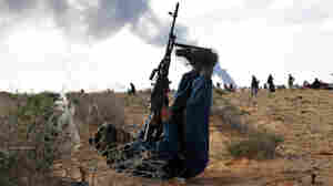 A Libyan rebel fighter uses his legs to steady his weapon as he fires at a fighter jet during clashes with pro-Gadhafi forces outside the oil town of Ras Lanuf.