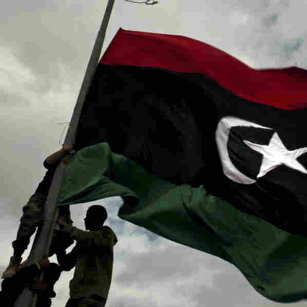 Rebel fighters in Libya raise a pre-Gadhafi flag Tuesday on the outskirts of the eastern town of Ras Lanuf.