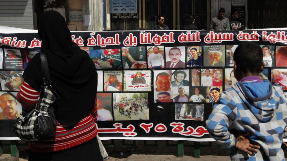 """Egyptians look at a banner that says """"Martyrs of the January 25th Revolution."""" The banner bears pictures of demonstrators who were killed during anti-government protests."""