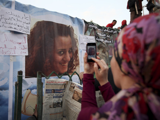 A woman in Cairo's Tahrir Square takes a picture of a poster of Sally Zahran, 23, who was killed in Egypt last month.