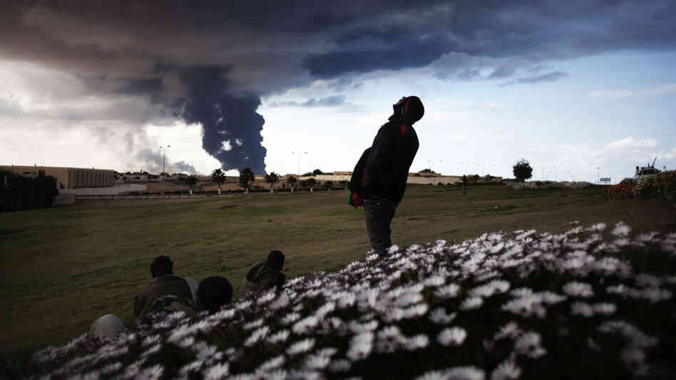 Libyan rebels watch as pillars of smoke rise from the oil facility just outside the town of Ras Lanuf on Wednesday.
