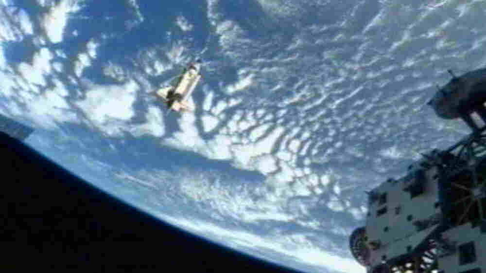 The space shuttle Discovery(C) departs the International Space Station on March 7, 2011.
