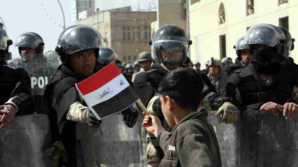 A young Iraqi holds a national flag in front of security forces as thousands gather in Baghdad on March 4 to protest corruption, unemployment and poor public services. After cracking down on earlier protests, Prime Minister Nouri al-Maliki has changed his tone.