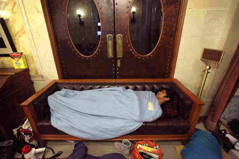 A protester sleeps in front of the doors to the Wisconsin state Assembly chamber, hoping to block access before the session reconvened later in the morning.