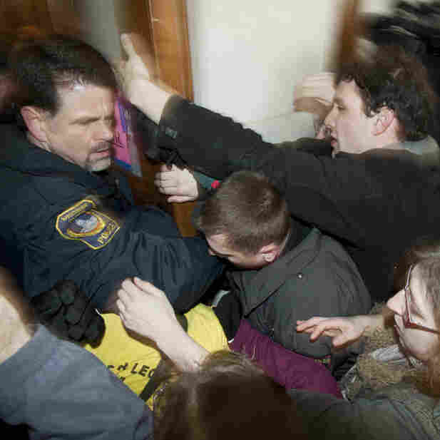 Wisconsin police tried to secure a door inside the state Capitol as thousands of angry people mobbed the area in anticipation of Thursday's Assembly vote.