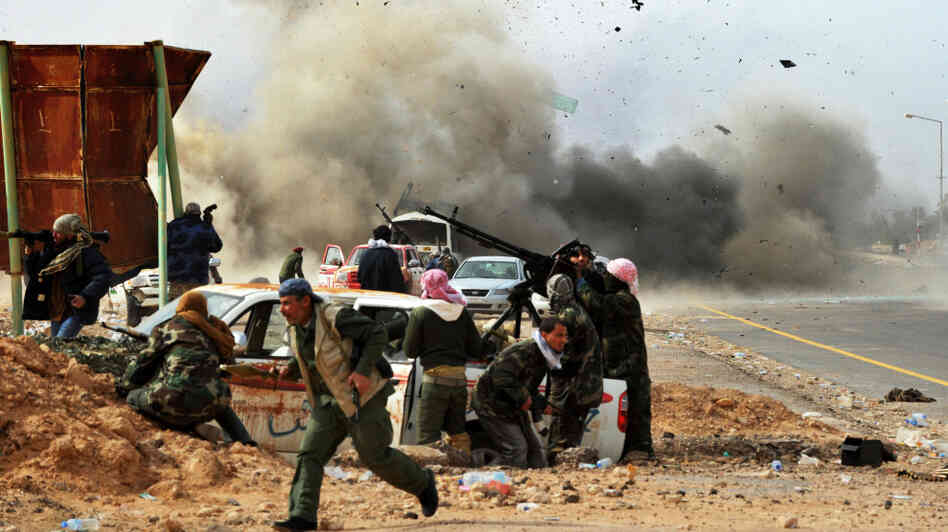 Shrapnel flies through the air as a tank shell explodes near Libyan rebel fighters defending their last position against Gadhafi's loyalist forces at Ras Lanuf on Thursday.