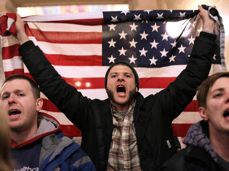 A protester shouts as he holds an American flag after storming the Wisconsin State Capitol on Tuesday.  The Wisconsin Republican Senators voted to curb collective bargaining rights for public union workers in a surprise vote with none of the missing Democrats present.