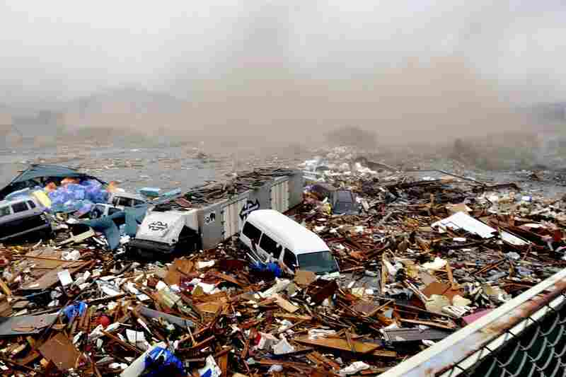 Cars and other debris swept away by a tsunami pile up in Kesennuma.