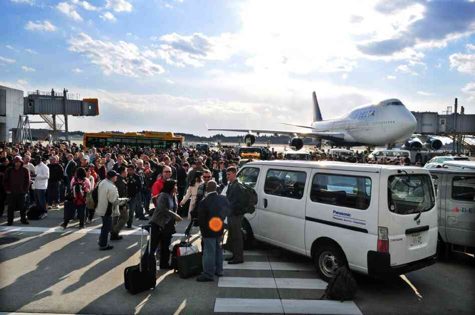Travelers stand on the tarmac after Narita International Airport in suburban Tokyo was evacuated.