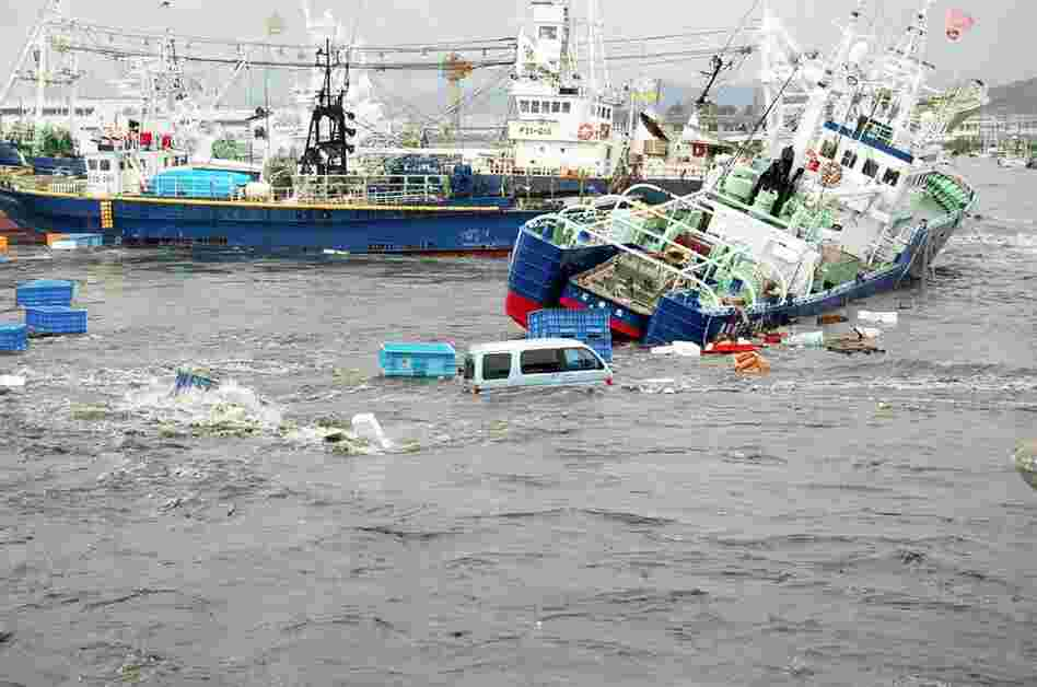 Fishing boats and vehicles are carried by a tsunami wave at Onahama port in Iwaki city, in Fukushima prefecture, northern Japan.