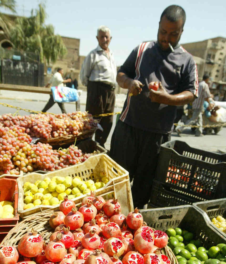 "An Iraqi cuts a pomegranate on his fruit stall at the Al-Shorja market, central Baghdad, in 2007. In her book Day of Honey, author Annia Ciazadlo says she visited the local Bagdhad markets when first arriving as a reporter in order ""to to comprehend the place I've landed in, to touch and feel and take in the raw materials of my new surroundings."""