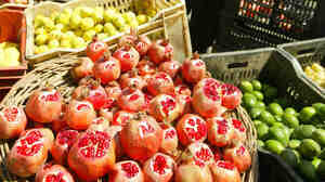 """An Iraqi cuts a pomegranate on his fruit stall at the Al-Shorja market, central Baghdad, in 2007. In her book Day of Honey, author Annia Ciazadlo says she visited the local Bagdhad markets when first arriving as a reporter in order """"to to comprehend the place I've landed in, to touch and feel and take in the raw materials of my new surroundings."""""""