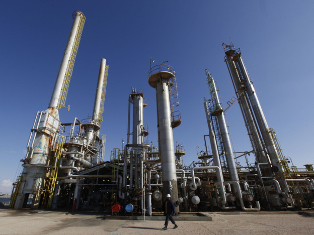A worker walks in front of a refinery inside the Brega oil complex in Libya. Events in North Africa and the Middle East are being closely watched by oil traders to determine what a barrel is worth.
