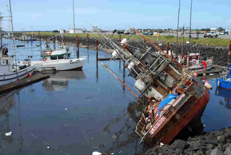 A fishing boat lies on its side in shallow water in the boat basin at Crescent City, Calif., after a tsunami surge withdrew Friday.