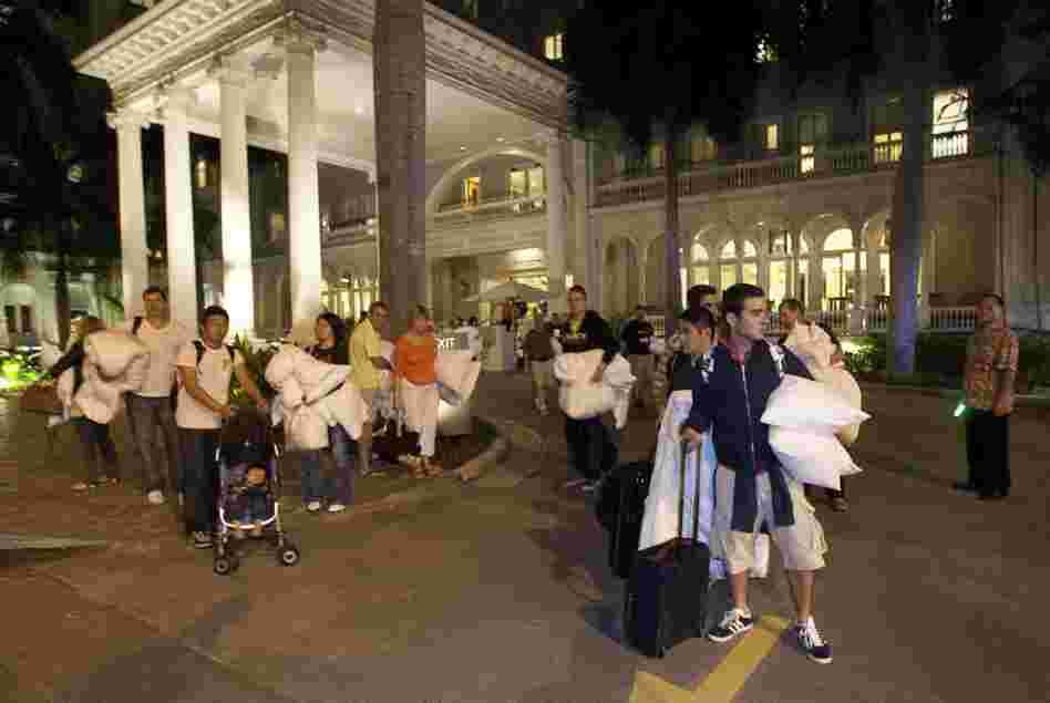 Hotel guests from the Moana Surfrider evacuate early Friday in Honolulu. The National Weather Service issued tsunami warnings for 50 countries and territories.