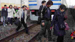 After a powerful earthquake forced train services to cease, commuters walk on railway tracks in Funabashi city, suburban Tokyo.