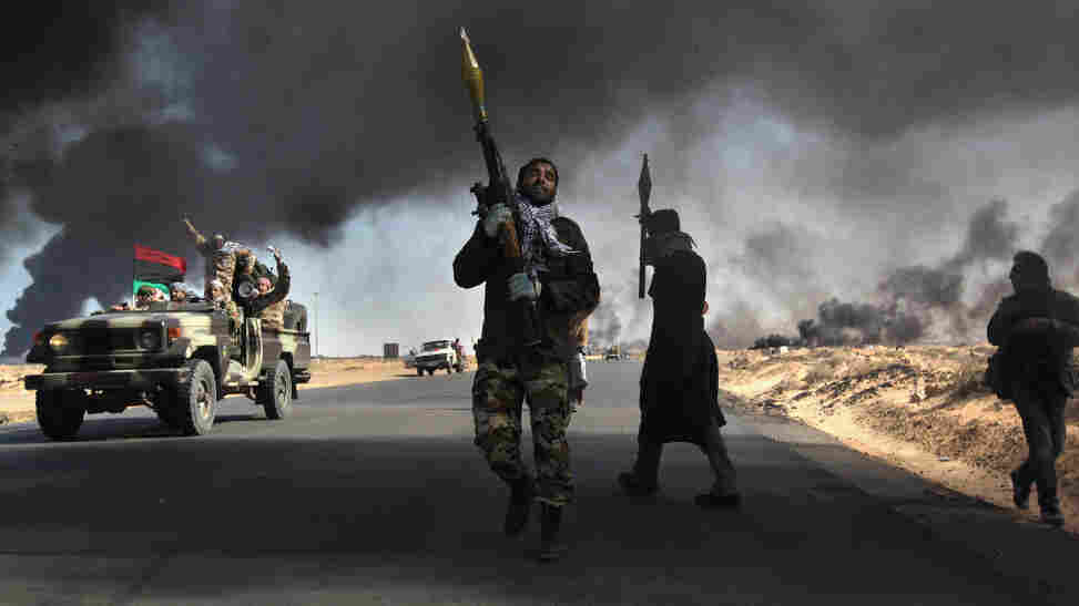 Libyan rebels battle government troops as smoke from a damaged oil facility darkens the front-line sky Friday in Ras Lanuf, Libya.