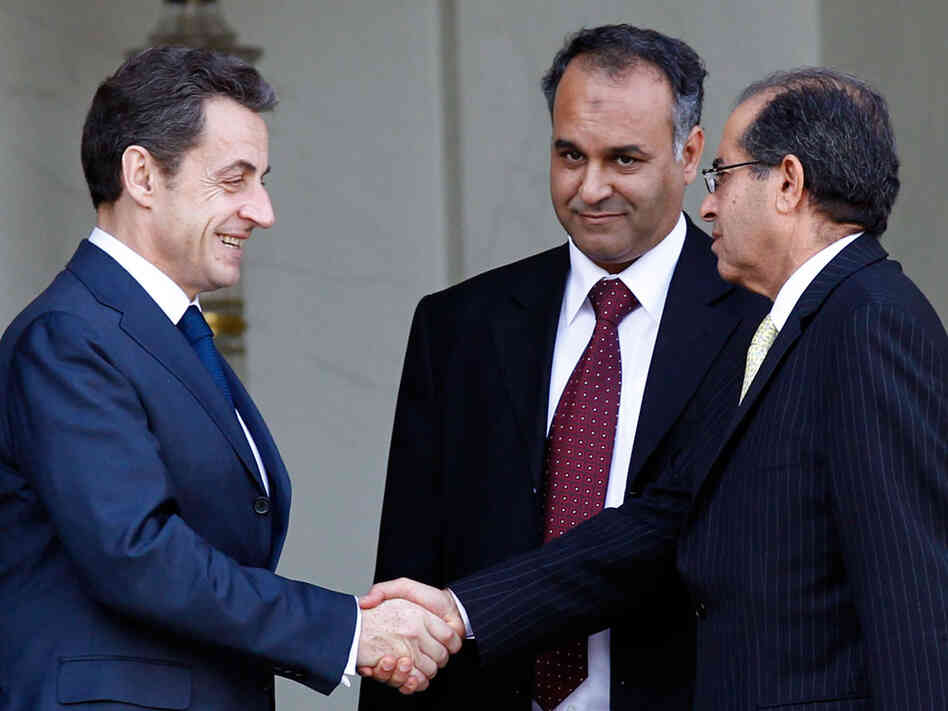 French President Nicolas Sarkozy (left) shakes hands with Mahmood Jibril (right) and Ali Al Issawi, representatives  of the newly formed Interim Transitional National Council in Libya, after  a meeting at the Elysee Palace in Paris on March 10.