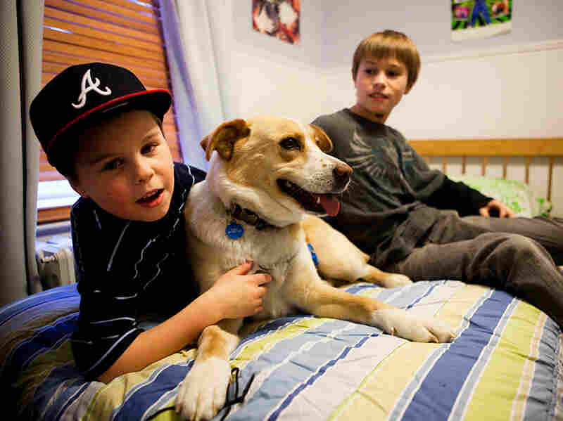 Tyler Scorza lounges on his bed with his older brother, Joe, and their dog, Casey.