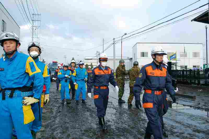 Rescue workers search for missing people in Sendai. Police said between 200 and 300 bodies were found along the coast.