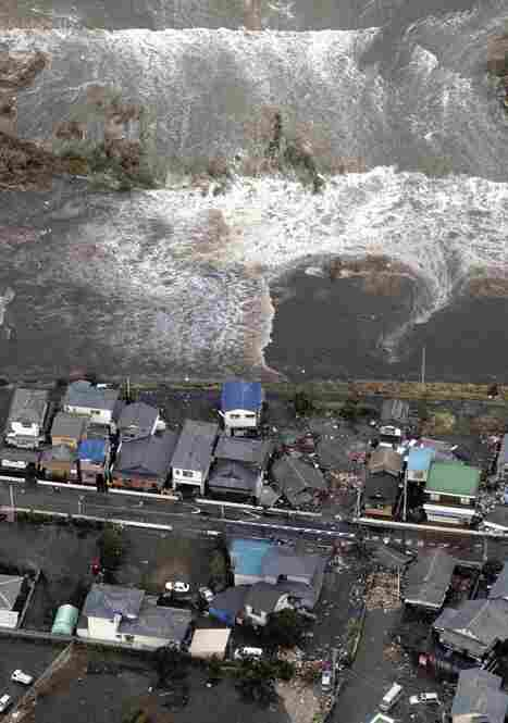 A tsunami approaches seashore houses in Kita Ibaraki, Ibaraki prefecture, northeast of Tokyo.