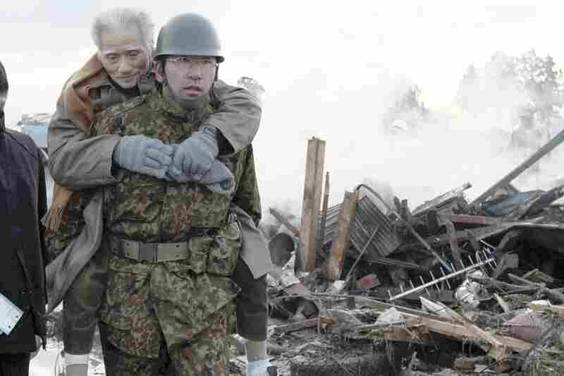 A self-defense force member assists a victim in the city of Natori in northern Japan.