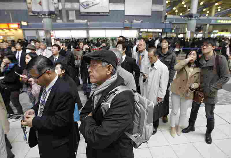 Train passengers wait at Tokyo's Shinagawa station. Train service and other public transportation was halted following the earthquake.