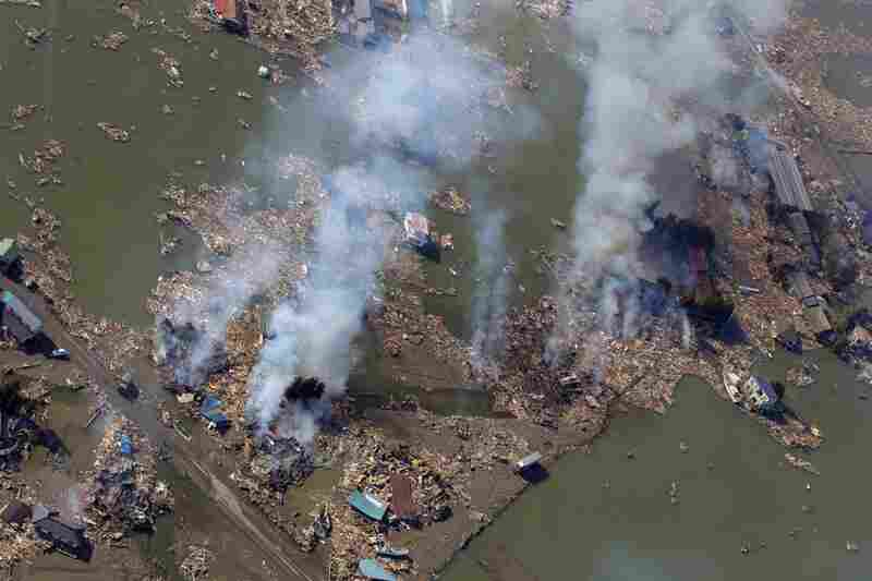 Smoke rises over a flooded area in Sendai.