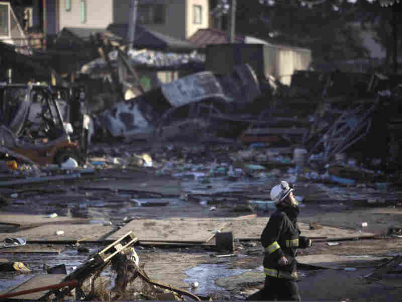 A firefighter runs against a background of damage from  a massive tsunami triggered by a powerful earthquake in Sendai in northern Japan.