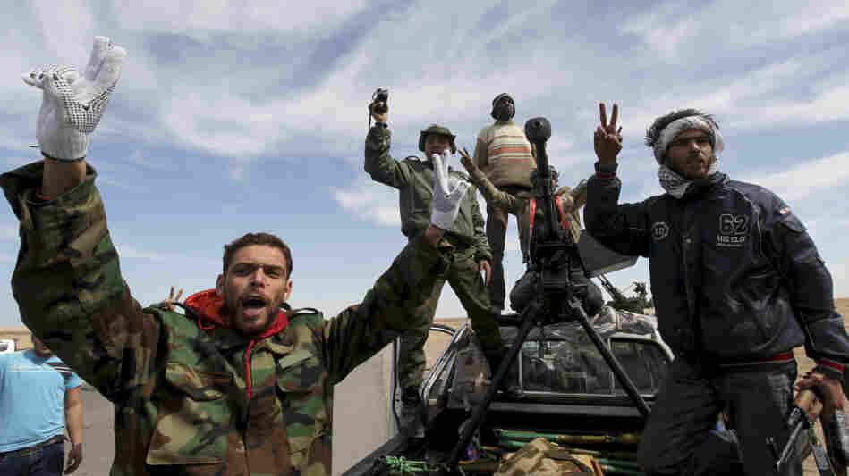 Anti-Gadhafi rebels stand at a desert road between Agela and Ras Lanuf in eastern Libya on Saturday.