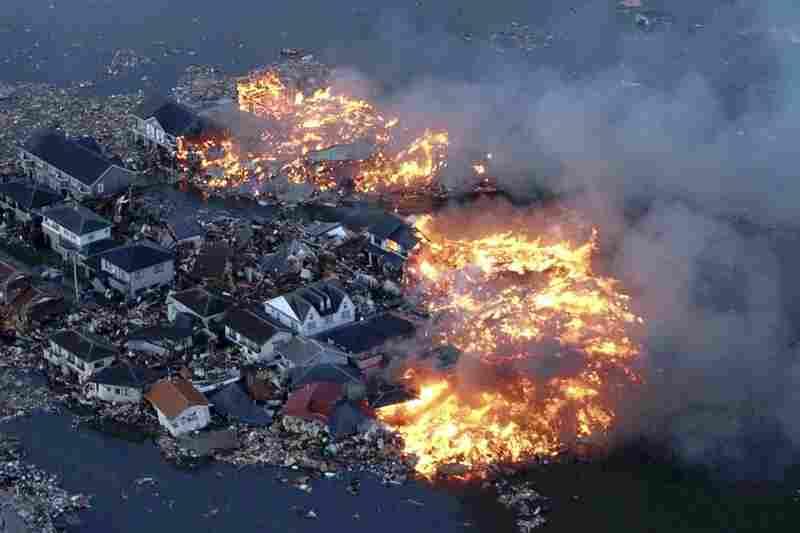 Houses burn while the Natori river floods in Natori City, Miyagi prefecture.