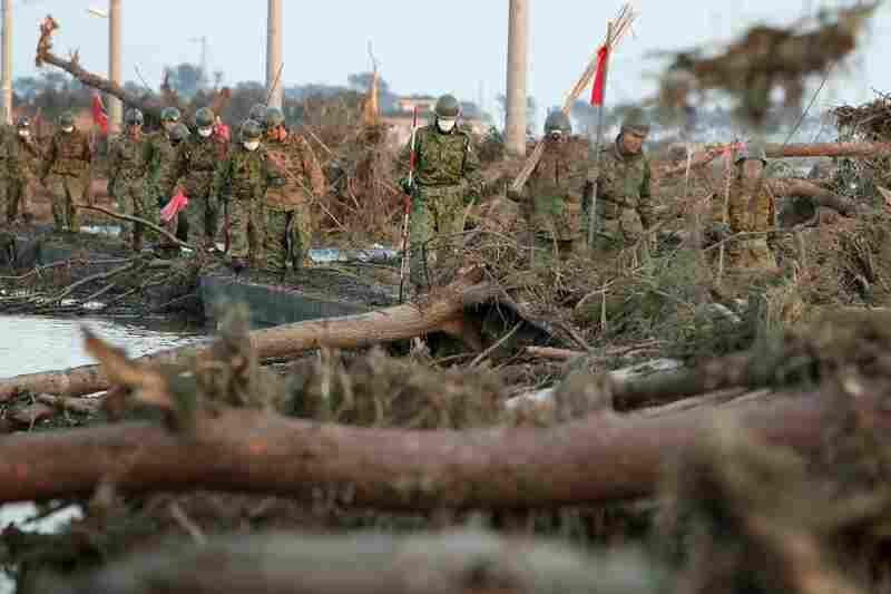 Members of the Japanese military walk through tsunami wreckage in Sendai, Japan on Sunday.