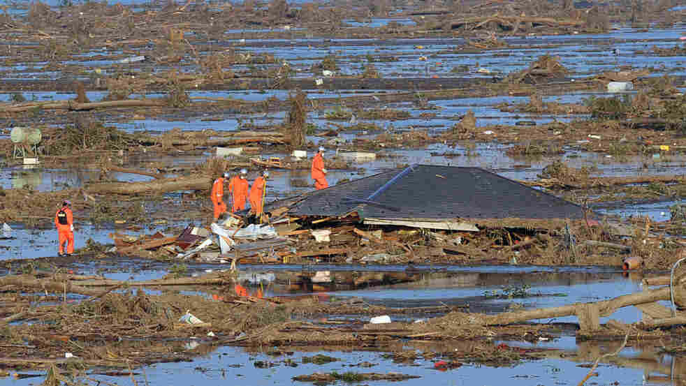 Rescue workers check the remains of a house for any possible survivors in Natori, Miyage prefecture, Sunday.
