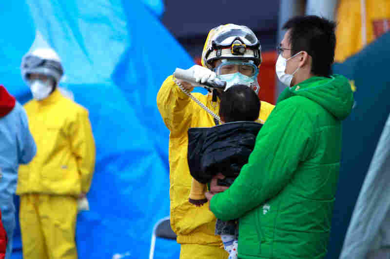A child is checked for radiation exposure. More than 200,000 people in the area surrounding the reactors have been evacuated.