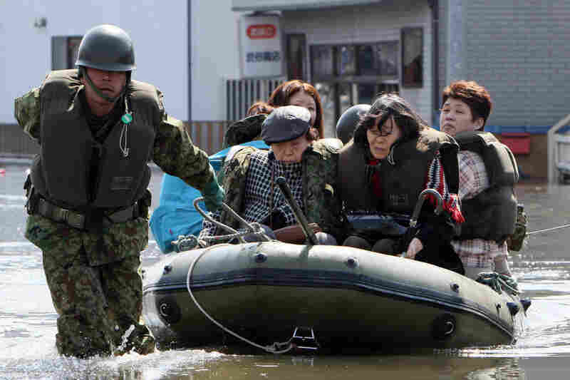 A soldier pulls evacuated people in a rubber boat at Ishinomaki city in Miyagi prefecture.