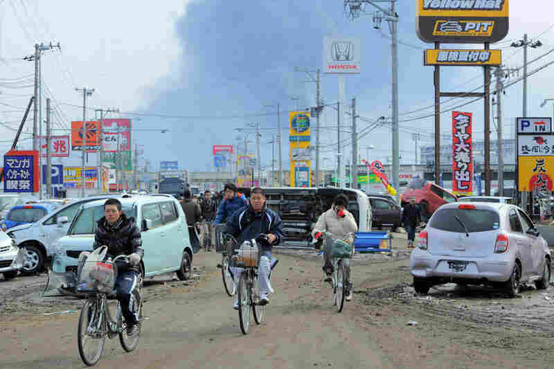 Local residents cycle past damaged cars littering a street in Tagajo, Miyagi prefecture, as fire smoke rises in the distance.