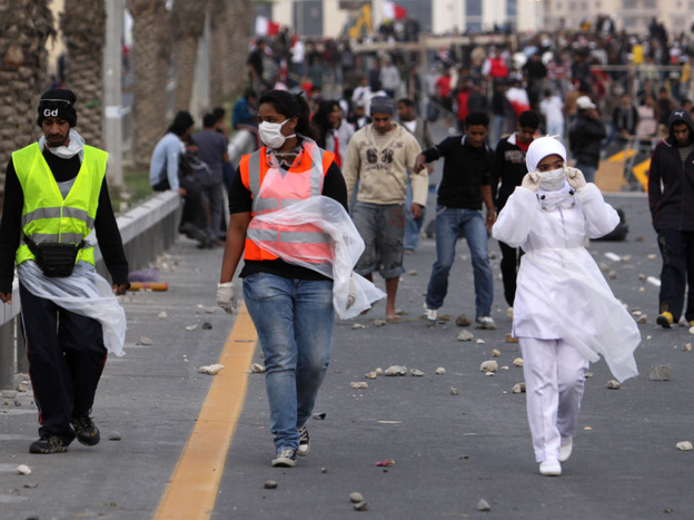 A Bahraini nurse (right) walks with anti-government protesters heading onto the streets of Manama to await a Saudi-led military force that crossed into Bahrain on Monday.
