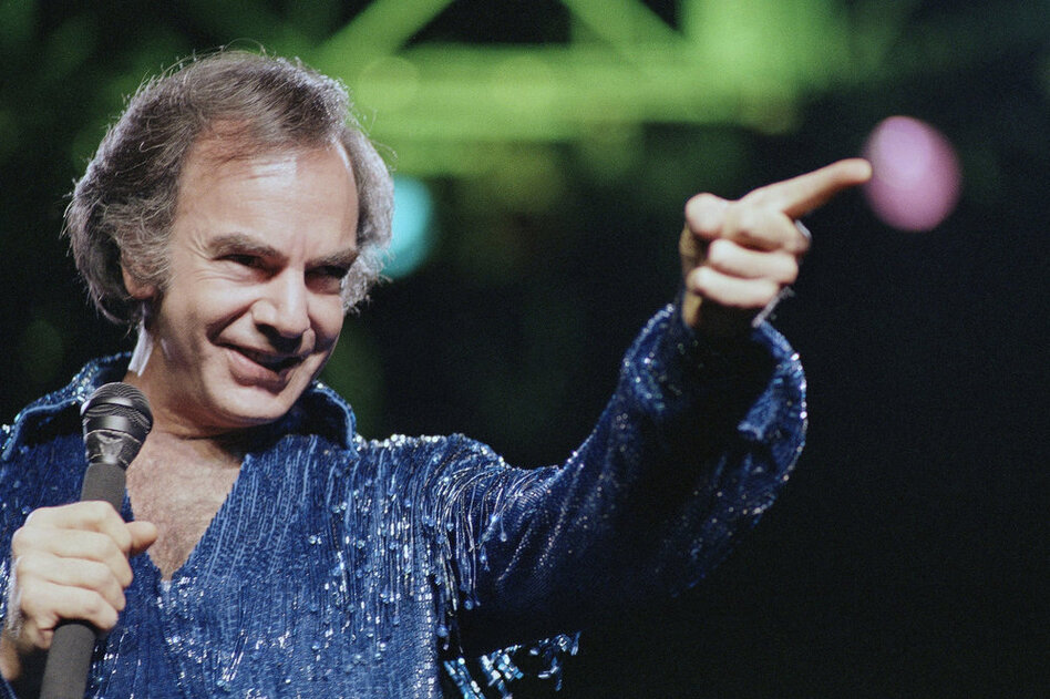 "Diamond continued to churn out present-day classics like ""Holly Holy"" and ""Song Sung Blue,"" which reached No.1 on the Hot 100. After performing in sold-out venues, Diamond released Hot August Night in 1972, an album critics hail as ""the ultimate Neil Diamond record."" Here, Diamond performs at New York's Madison Square Garden in 1986.  (AP)"
