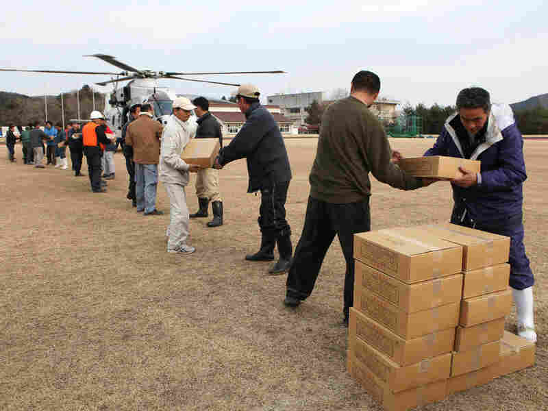Local residents and town staff carry out relief supplies from a helicopter in the town of Onagawa in Miyagi prefecture on Monday, three days after a massive 8.9 magnitude earthquake and tsunami devastated the coast of eastern Japan.