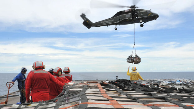 Sailors aboard the U.S. 7th Fleet command ship USS Blue Ridge stand by to move pallets of humanitarian relief supplies across the ship's flight deck.