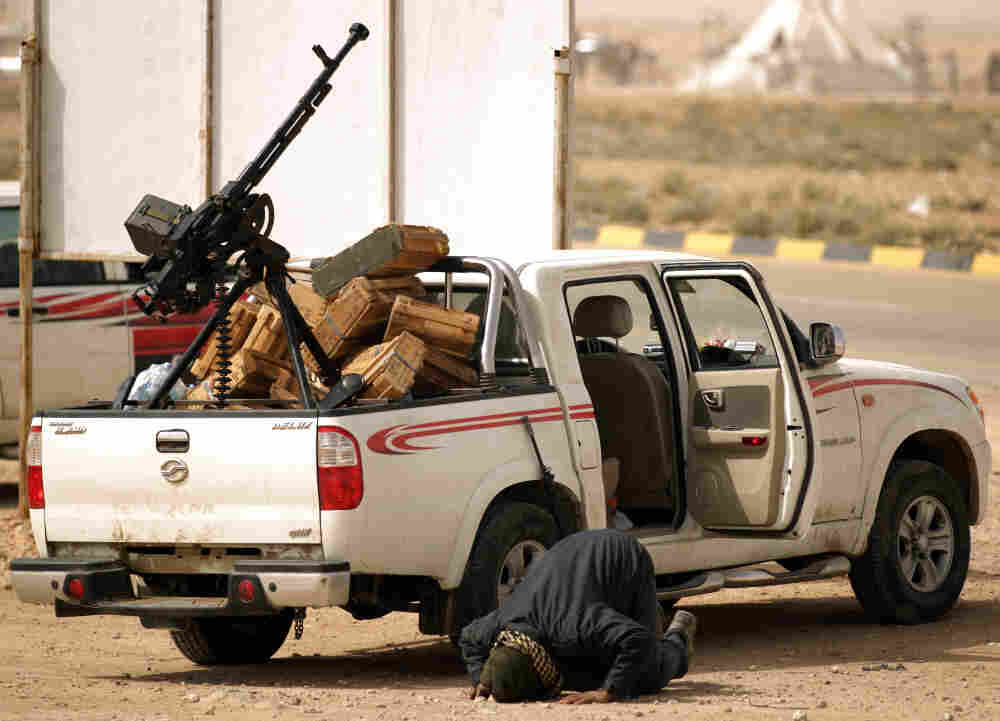 A Libyan rebel prays next to a pick-up truck loaded with a machinegun in Ajdabiya, a key town which the rebels have vowed to defend at all costs from forces loyal to Libyan leader Moamer Gadhafi.
