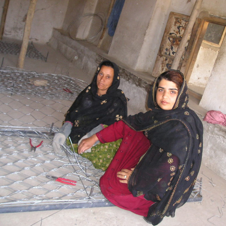 Kamila Sidiqi (foreground) teaches gabion-making while working with Mercy Corps. Sidiqi started her own business making clothes in Kabul while Afghanistan was under repressive Taliban rule, eventually employing over 100 women in her neighborhood.