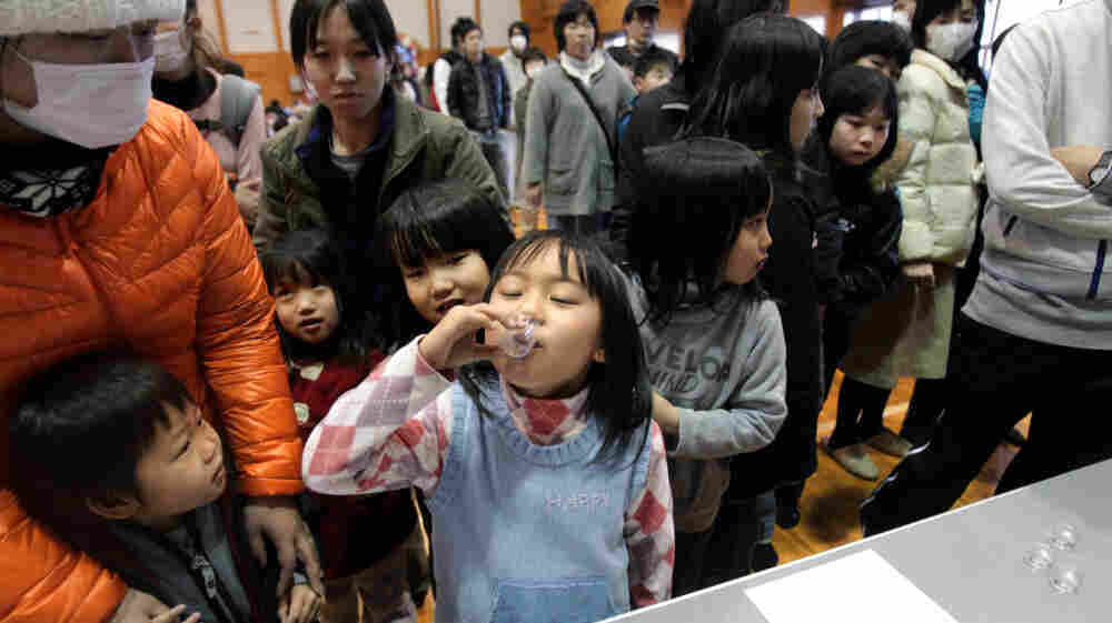 Children in Kawamata, Japan, take potassium iodide on Monday to protect against thyroid cancer after being evacuated from the vicinity of the Fukushima Daiichi Nuclear Power Plant.